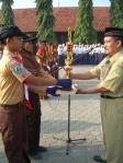 Dimas mempersembahkan piala Juara Lomba Pramuka Kabupaten Kepada Kepala Madrasah